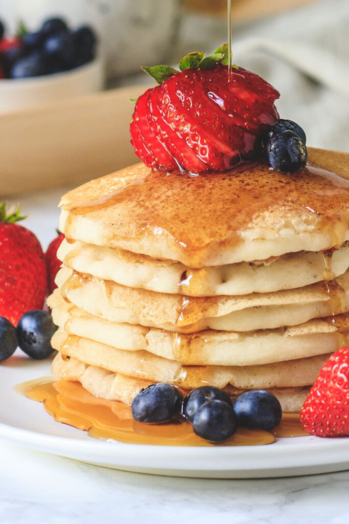 stack of eggless pancakes with berries and syrup