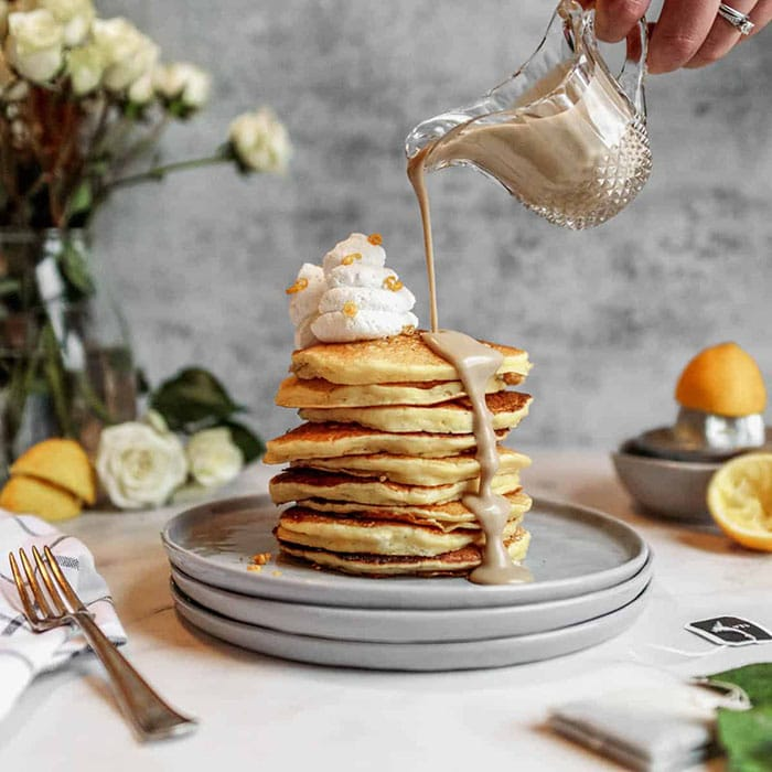 stack of lemon buttermilk pancakes with earl grey creme anglaise being poured on this unique pancake recipe