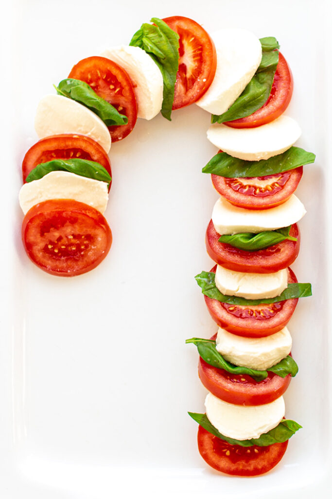 caprese salad formed into a candy cane on a white platter