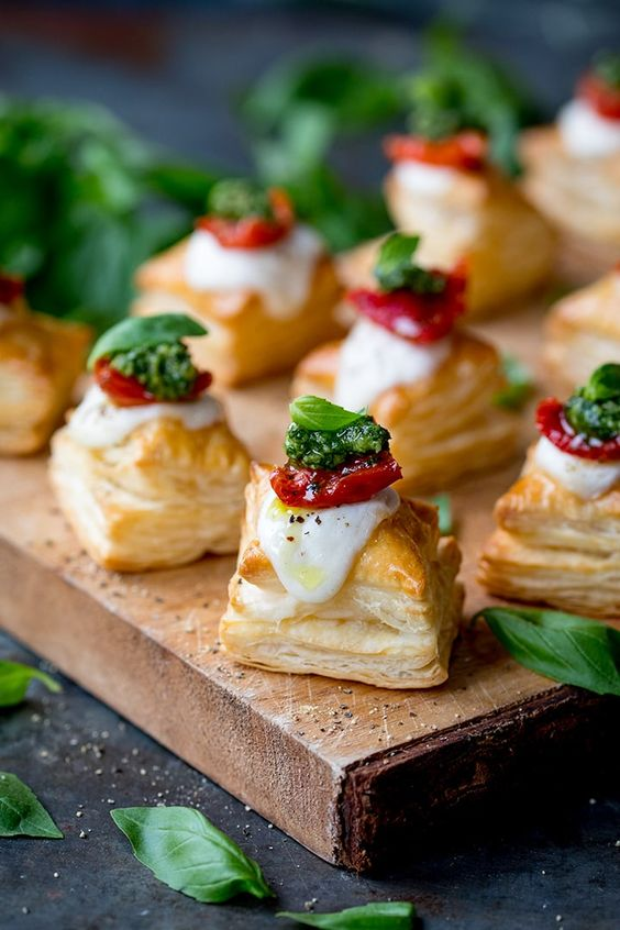 mozzarella tomato and basil on a puff pastry square served on a wood platter