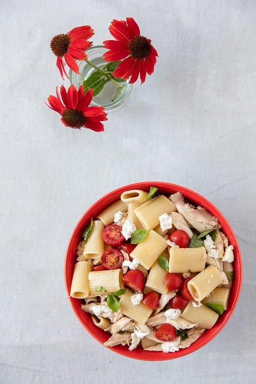 pasta with tomato basil and mozzarella in red bowl