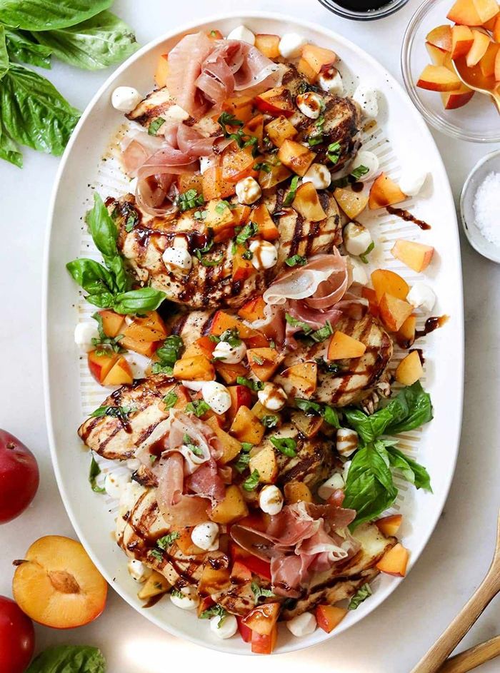 platter with stone fruit, prosciutto, grilled chicken and fresh basil leaves