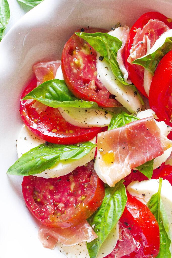 layers of tomato, prosciutto, mozzarella and basil in this unique caprese salad