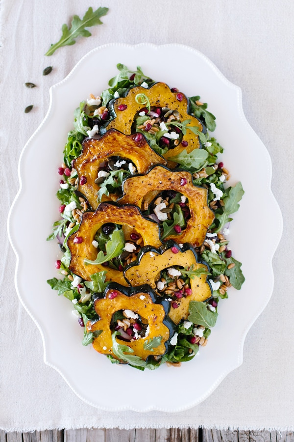 An oval salad plate of Roasted Acorn Squash Salad with Spicy Pepitas and Cranberries is photographed from the top on a farm-style table.