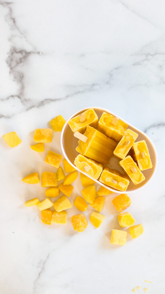container filled with orange colored mango popsicles